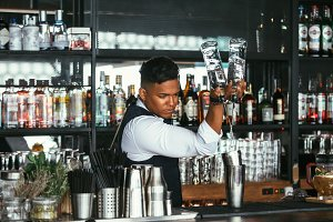 Expert barman adds alcohol to shaker