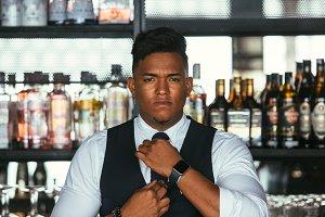 Elegant expert bartender put on tie