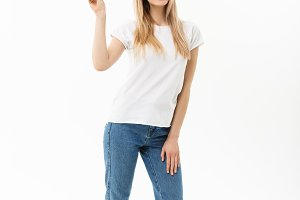 Full length portrait of a happy young woman standing and showing peace gesture with two hands isolated over white background