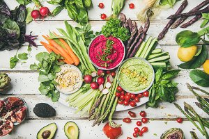 Chickpea, beetroot, spinach hummus dips with colorful vegetables and greens