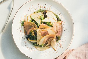 Summer salad with smoked turkey ham and pear, white background