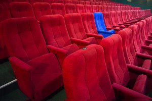 Blue chair between rows of red seats