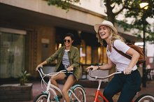 Female friends enjoying bicycle ride by Jacob Lund in People