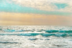 Sunset on the blue sea with waves