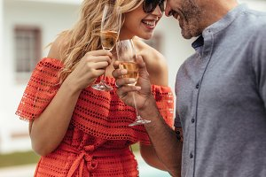 Romantic couple toasting glasses