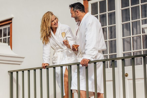 Couple in bathrobes drinking wine