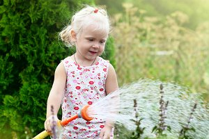 Little girl watering the grass