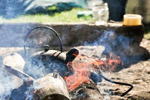 Black kettle tea pot on fire wood outdoor