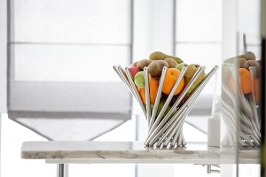fruits in the metal vase on the table in the light room, fresh pomegranate, pear, apples, tangerine