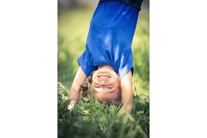 Happy little girl standing upside down on grass in summer park