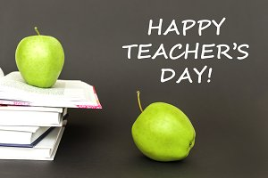 text happy teacher's day, two green apples, open books with concept