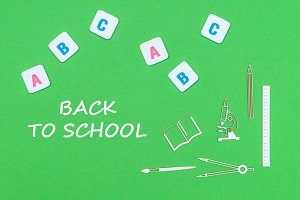 text back to school, from above wooden minitures school supplies and abc letters on green background