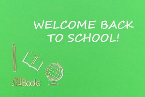 text welcome back to school, school supplies wooden miniatures on green background