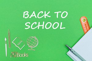 text back to school, school supplies wooden miniatures, notebook on green background