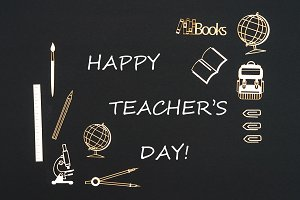 School supplies placed on black background with text happy teacher's day