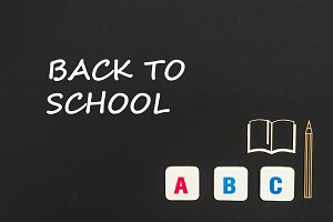 abc letters and chipboard miniature on blackboard with text back to school