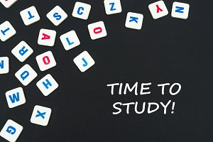 english colored square letters scattered on black background with text time to study