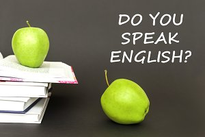 text do you speak english, two green apples, open books with concept