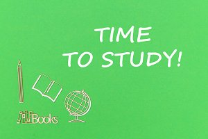 text time to study, school supplies wooden miniatures on green background