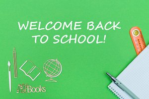 text welcome back to school, school supplies wooden miniatures, notebook on green background