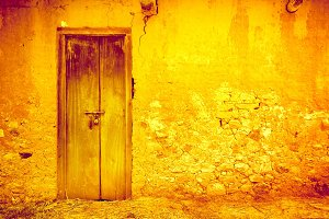 Cracked yellow wall with door. Vintage background.