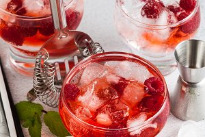 summer alcoholic drink with raspberry liqueur, ice and leaves of