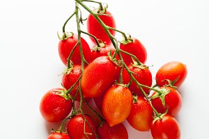 a bunch of small wet cherry tomatoes isolated on white