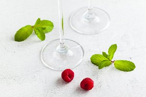 close up food background with glass legs , fresh raspberries and