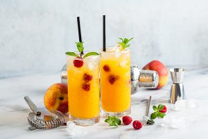 two refreshing drinks from peach juice and raspberries with fres