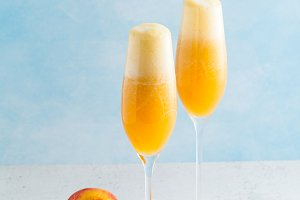 two glasses of champagne with a cocktail of Bellini and fresh pe