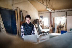 Portrait of a woman worker with laptop in the carpentry workshop.