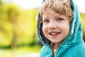 A happy toddler boy outside in spring nature. Close up.