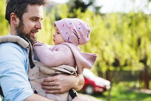 A father with his toddler daughter in a baby carrier outside on a spring walk.