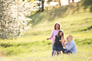 Senior couple with grandaughter outside in spring nature.