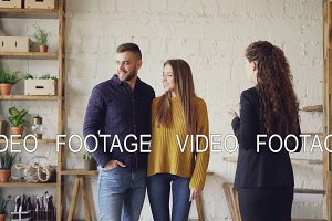 Female realtor in suit is showing loft style flat to young man and woman looking for new apartment. Buyers are excited about interior, they are smiling and talking.
