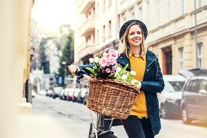 Young woman with bicycle and flowers in sunny spring town.