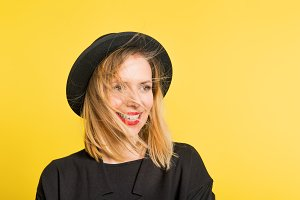 Portrait of a young beautiful woman with black hat in studio on a yellow background.