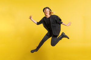 Young beautiful woman with black hat in studio on a yellow background, jumping.