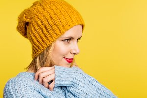 Portrait of a young beautiful woman with a woolen hat in studio on a yellow background.
