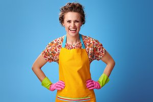 Portrait of smiling modern housewife with rubber gloves on blue