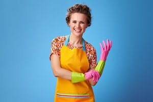 happy young housewife pulling on rubber glove on blue