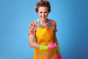 smiling young woman with rubber gloves on blue bowing