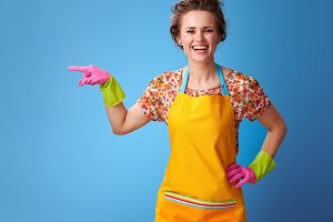 happy modern housewife pointing at something on blue