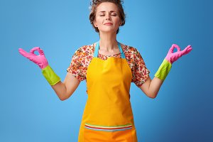 relaxed young housewife in yellow apron on blue doing yoga