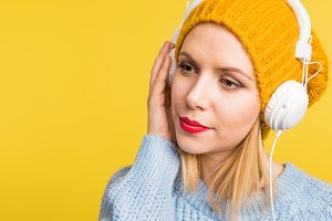 Portrait of a young beautiful woman with headphones in studio on a yellow background.