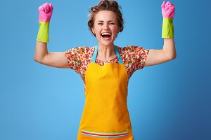 smiling young housewife in yellow apron rejoicing on blue