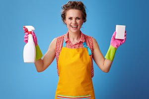 smiling housewife showing cleaning sponge and detergent on blue