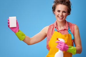 housewife with cleaning detergent using kitchen sponge on blue