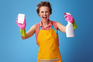 housewife showing cleaning sponge and detergent on blue