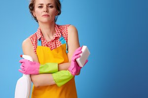 Cool woman with kitchen sponge and cleaning detergent on blue